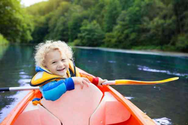 Child with paddle on kayak.