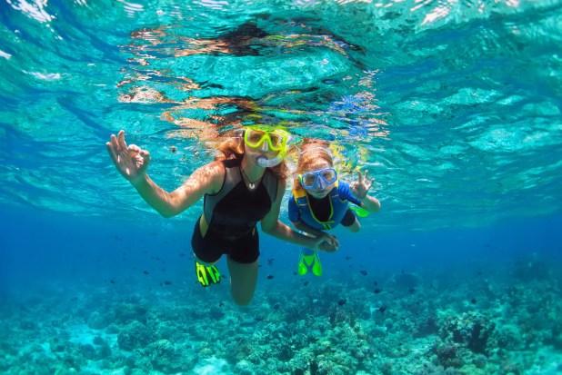 mother, kid in snorkeling mask dive underwater