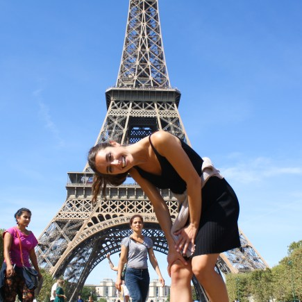 Ellen posing and laughing at the Eiffel Tower in Paris, France for Ellen Blazer's travel blog To Travel and Bloom