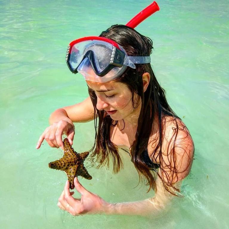 Ellen with a starfish found at Eagle Beach, Aruba for Ellen Blazer's travel blog To Travel and Bloom
