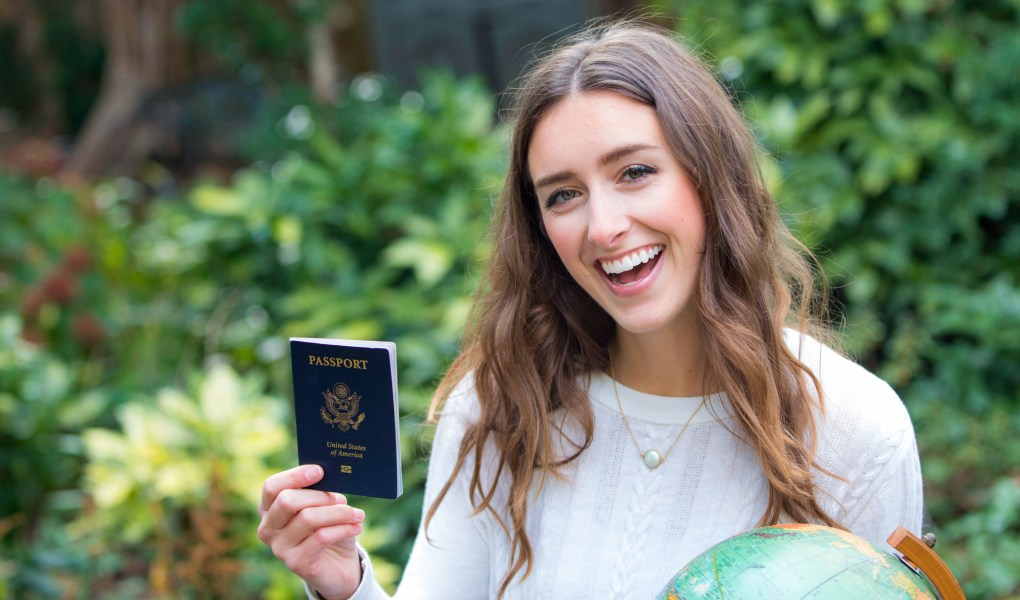 Posing with a passport and globe for Ellen Blazer's travel blog To Travel and Bloom