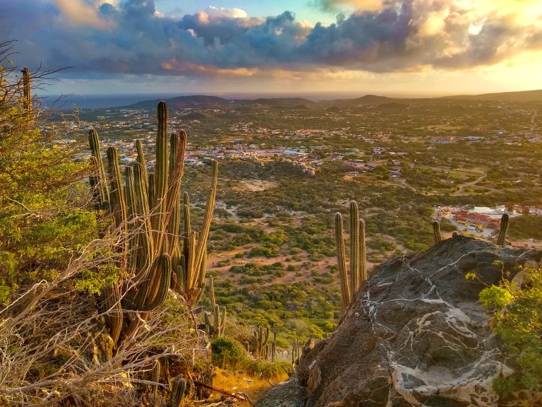 Watching the sunrise from the peak of Hooiberg in Aruba for Ellen Blazer's travel blog To Travel and Bloom