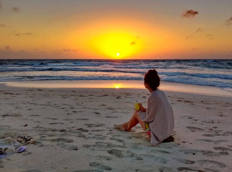 Ellen watching the sunrise, coffee in hand, from Bachelor's Beach, near Baby Beach, Aruba, for Ellen Blazer's travel blog To Travel and Bloom
