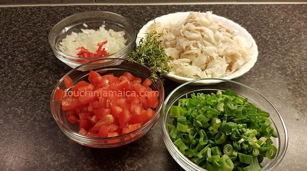 Zutaten für jamaikanische Saltfish Fritters - von links oben im Uhrzeigersinn: Zwiebel und Chili; Saltfish; Lauchzwiebeln; entkernte Tomaten; in der Mitte: Thymian.