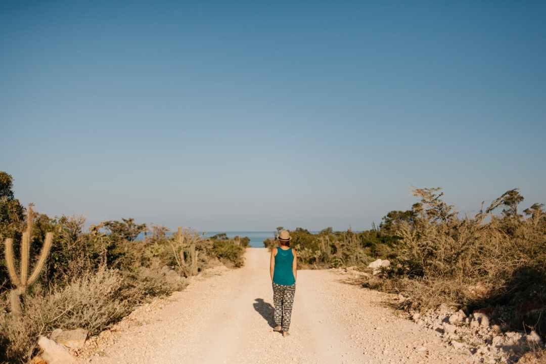 woman walking on dusty road towards sea