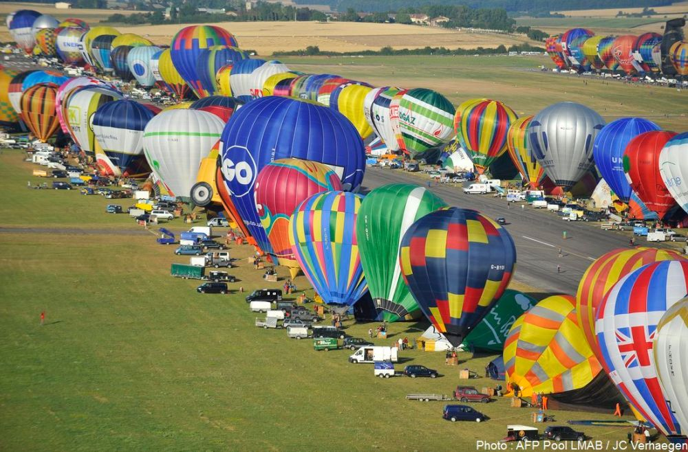 "Hot-air balloons fly near Chambley-Bussieres airbase, eastern France, on July 26, 2015 , for the first day of the biennial ""Lorraine Mondial Air Ballons"", an international air-balloon meeting.  POOL AFP PHOTO / JEAN-CHRISTOPHE VERHAEGEN"