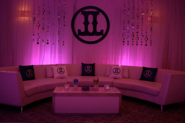 Curved-couch-personalized-pillows-logo-cut-out-drapes-with-lighting-and-foil-dot-curtains