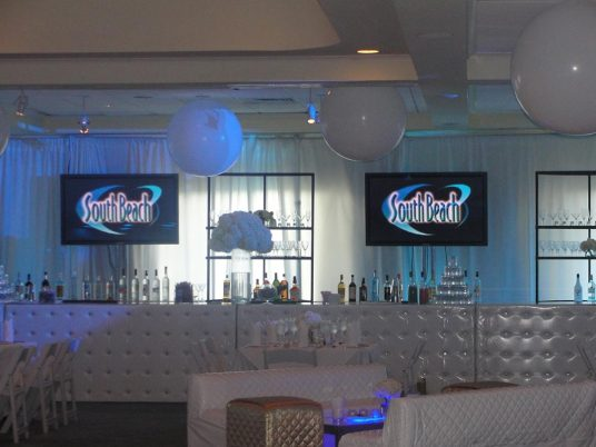 White-orbs-tufted-bars-and-video-screens-at-catered-event