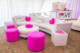 white-curved-couch-pink-ottomans