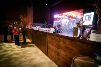 Giant-Video-screen-behind-full-wooden-rustic-bar