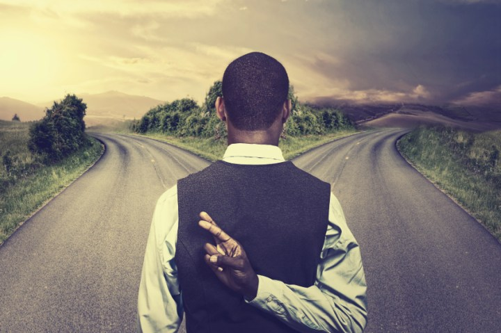 businessman in front of two roads fingers crossed