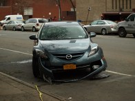 Damaged car on Avenue C between East 13th and 14th Streets. (Photo by Maria Rocha-Buschel.)