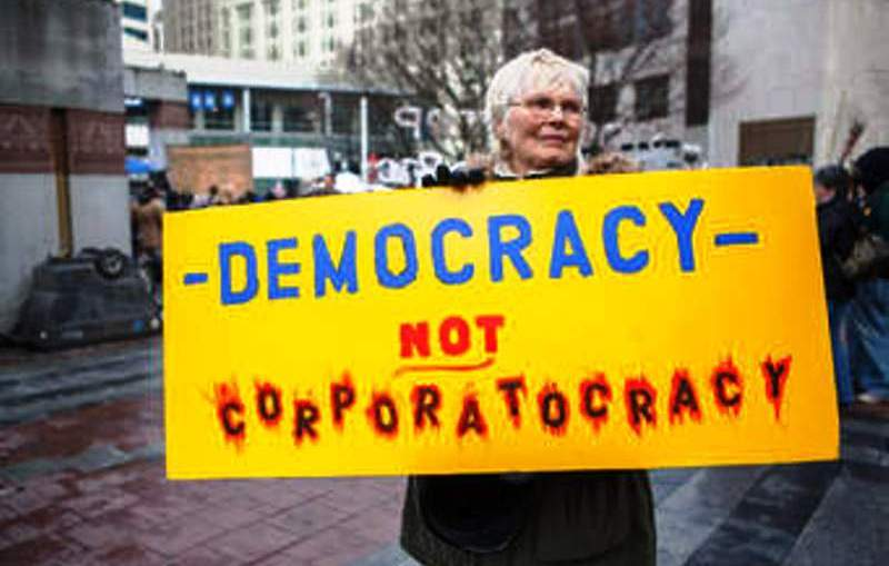 Woman demonstrates for democracy not Corporatocracy