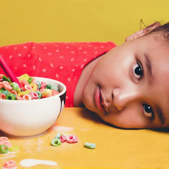 Child looking upset with head down on the table with cereal bowl close by. Fidgets can help with anxiety