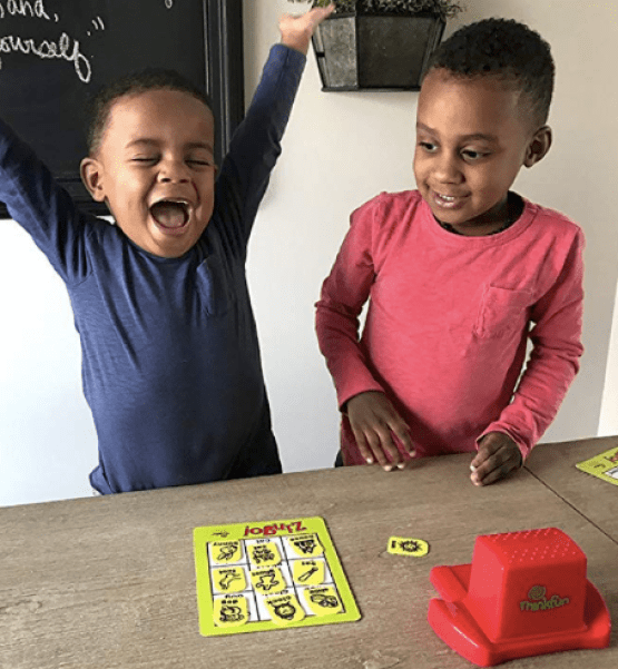Two kids playing the reading game Bingo to bolster their reading skills. One child has this hands up in the air as the clear winner of the game.