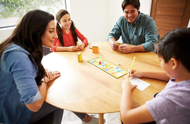 Family playing kids games to explain the rules and set procedures to ensure fair play for when kids play independently.