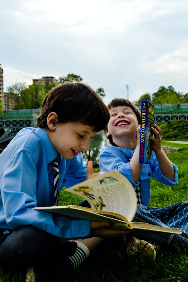 Two boys laughing while reading. No phonics workbooks, no phonics worksheets.