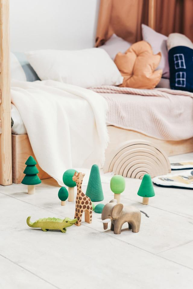 In a child's bedroom there are some animals set up for playtime. For beginning independent child's play you need to set up the scene for your kids.
