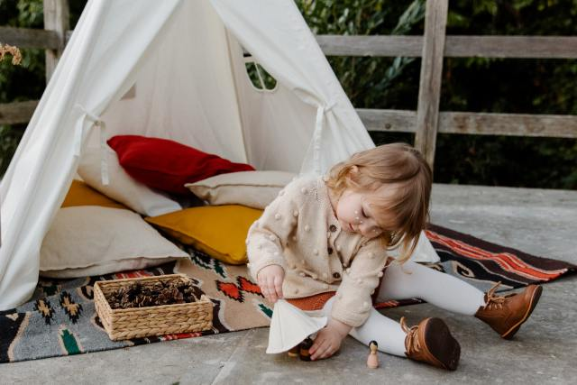 Young girl playing in her calming area, tent with pillows, and favourite toys. She is calm and engaged.