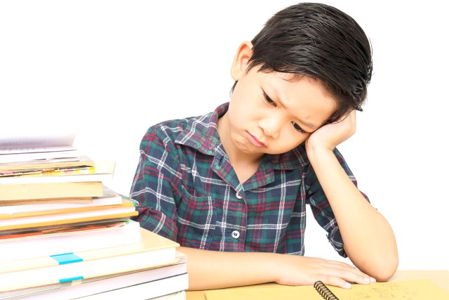 school aged boy looking frustrated, reluctant reader, possible learning disability