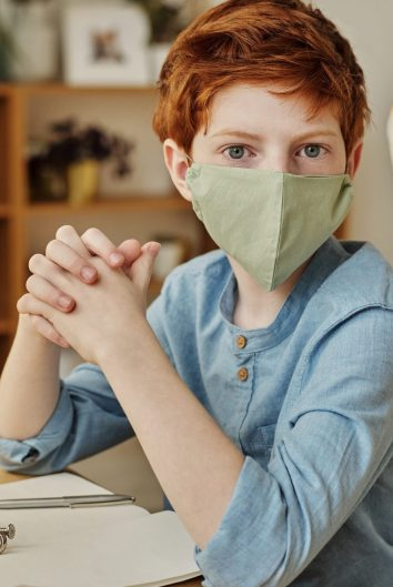 Red haired boy wearing a mask, sitting at a desk. Many schools will insist that all kids will need to wear masks to keep everyone safe.