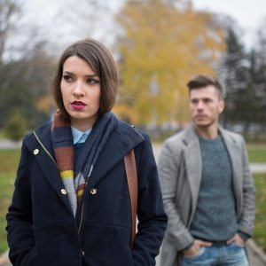 Photo of a Jealous Couple. A woman in front starting off in the distance and a man behind out of focus.
