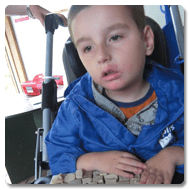 Joe is sat in his buggy, wearing a blue jacket, his hands are touching the mosaics that are placed in a tray on the Trabasack attached to his buggy