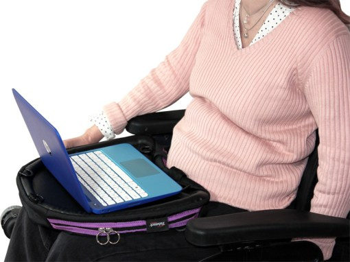 Image is a photograph of a lady wearing a peach-coloured, ribbed jumper, sitting in a wheelchair with a purple trim Trabasack Curve on her lap, using a laptop on the desk surface