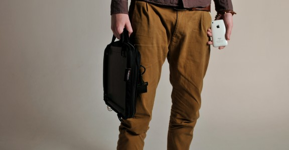 Image of a man holding Trabasack Mini briefcase in one hand, an iphone in the other
