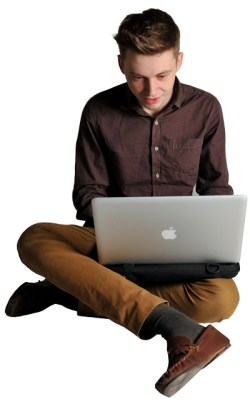 Young man sat cross-legged on the floor, using a laptop computer on top of a Trabasack lapdesk