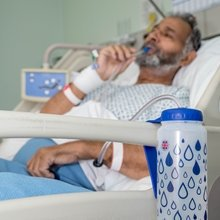 Image is a photograph of a man lay back in a hospital bed using the build-in straw with bite-valve to drink from a Hydrant water bottle