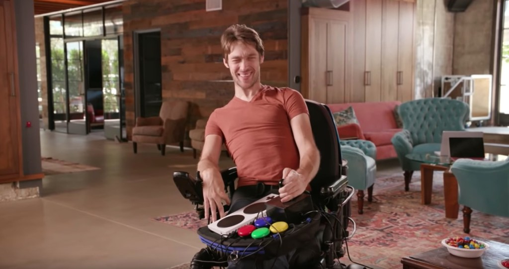 Zach Anner plays a video game in a spacious American lounge, using a Trabasack Curve Connect lapdesk and accessible gaming accessories