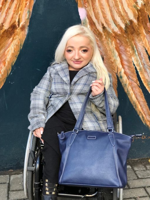 Photograph shows Sam Renke dressed in a plaid jacket and black trousers, seated in a wheelchair holding a Navy blue Samantha bag in her left hand.