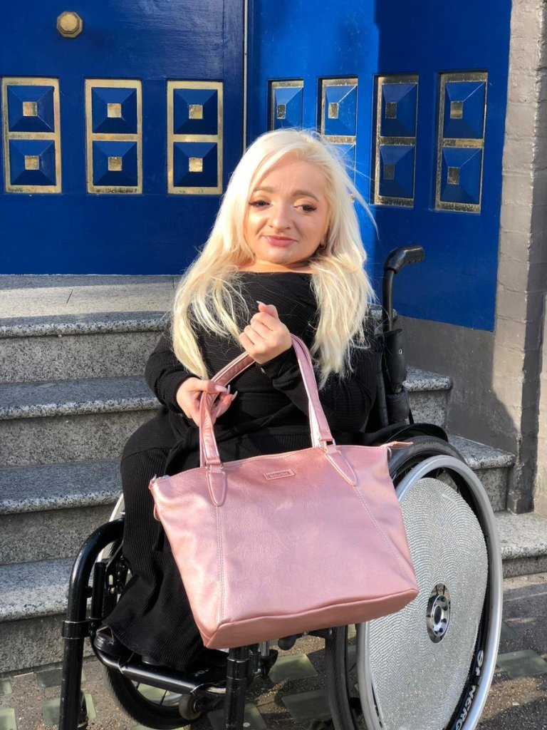Photograph of Sam Renke holding a bag from her Samantha Range in a Rose Gold colour, as she sits in her wheelchair at the base of a set of granite stairs