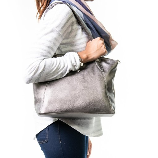 Photograph shows the side-view of a woman with a Metallic Grey Samantha Renke bag over the shoulder.