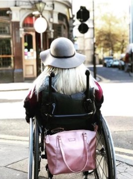 Photograph shows Sam Renke in a wheelchair from the back, with a Rose Gold Samantha Bag stored on the handles using the strap and mobility clips