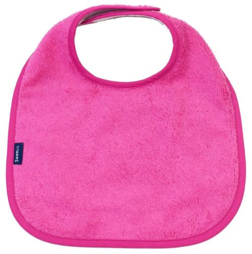 Image shows a photograph of a cerise pink, cotton towelling dribble bib lay flat on a white background