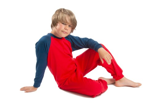 Image shows a photograph of a boy sat casually on the floor wearing a Seenin jersey sleepsuit in navy blue and red