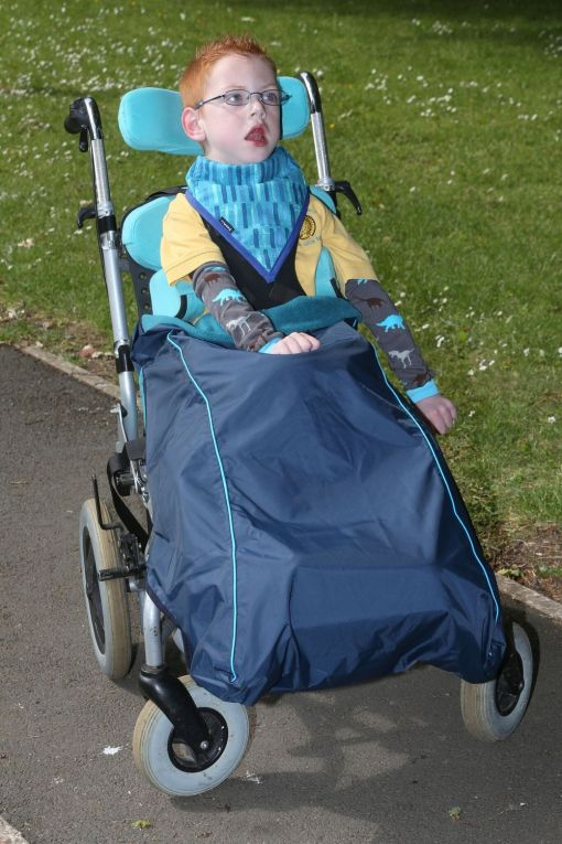 Image shows a photograph of a boy in an adaptive SEN stroller, sitting outdoors wearing a blue wheelchair leg protector