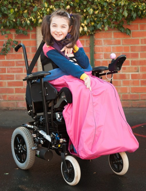 Image is a photograph of a cheerful girl with brown hair in bunches, sat outdoors in a wheelchair wearing a pink wheelchair leg cover