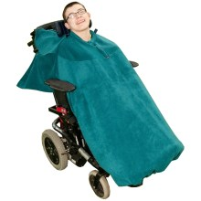 Image is a photograph of a young man smiling, sitting in a wheelchair with a teal full cover fleece
