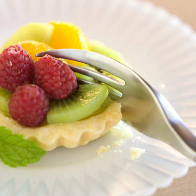 Image is a photograph of a Knork being used to cut through a fruit tart on a white dessert plate