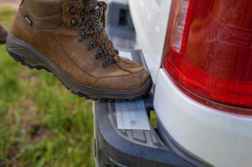 Image is a photograph of a boot standing on the rear footplate of a vehicle which has a strip of Cat Tongue Grip Tape attached to it