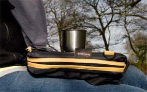 Image of the outdoors, with a cup resting safely upon the tray surface of the Trabasack Mini laptray bag with yellow trim