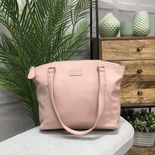Image is a photograph of the Samantha Renke accessible handbag in Blush on a white table in a modern living room