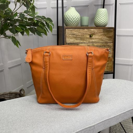 Image is a photograph of the Samantha Renke accessible handbag in Burnt Orange on a white table in a modern living room