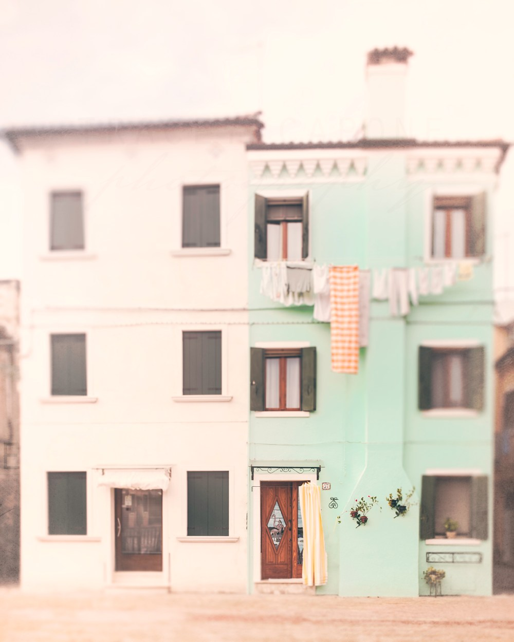 A mint green and white home with colorful laundry on the island of Burano, near Venice. Travel photography by Tracey Capone