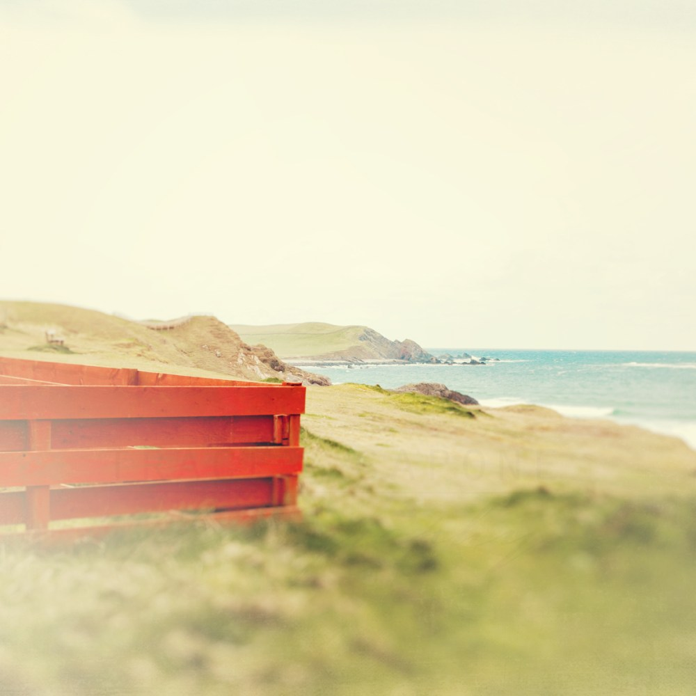 Photograph of a beautiful red wooden fence along the shores of Scotland, in the Highlands. Photography by Tracey Capone