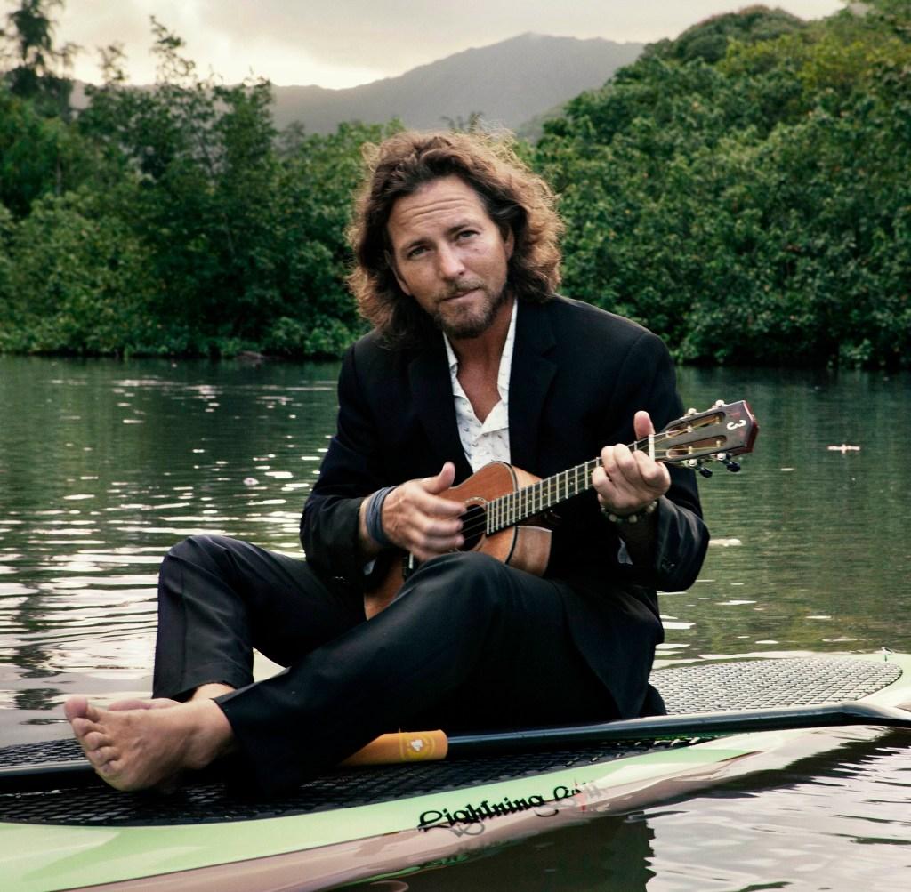 Eddie Vedder sentado em uma canoa sobre um rio, vestindo um terno preto, com um ukulele na mão e atrás dele uma floresta no dia nublado.