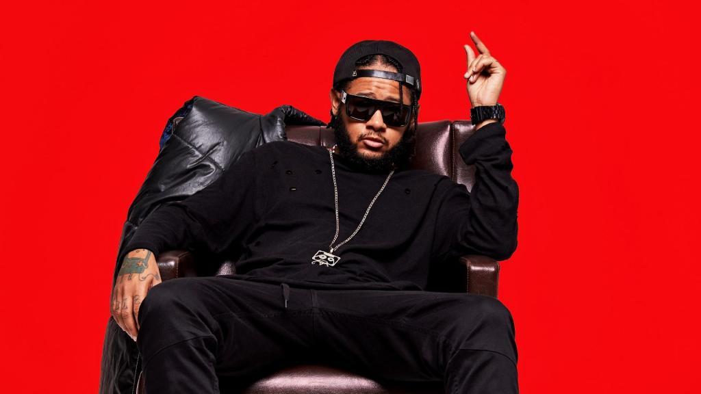 Emicida, numa foto promocional. O rapper está com uma vestimenta preta, com um fundo vermelho.